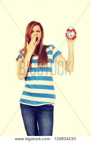 Yawning teenage woman holding alarm clock