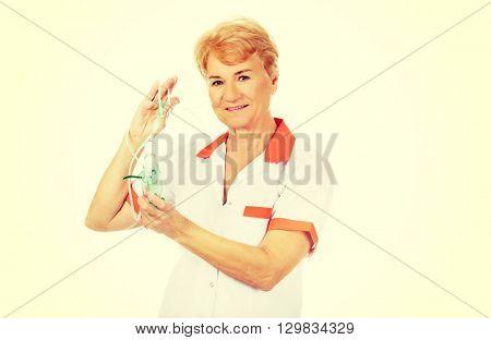 Smile elderly female doctor or nurse holds oxygen mask
