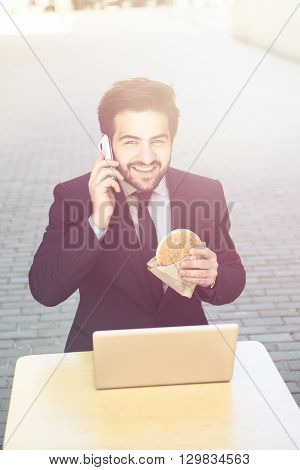 Toned picture of handsome businessman speaking over mobile or smart phone and eating hamburger. Young man sitting in front of laptop computer.