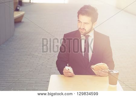 Toned picture of young confident businessman eating and drinkig in cafe. Handsome man sitting at table and looking away.