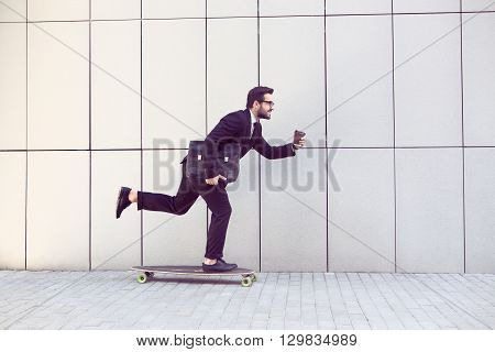 Toned image of businessman in black businesssuit on longboard walking with cup of coffee in his hand. Freelance man hurrying to his office.