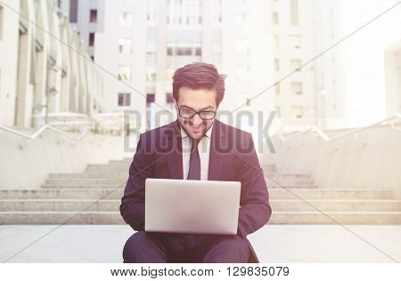 Closeup toned picture of handsome businessman working on his laptop computer and smiling. Freelance man looking ar screen and happy typing messages.