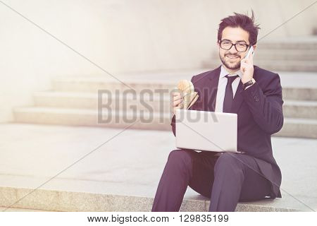 Toned portrait of handsome businessman in glasses looking at camera while working on laptop computer and eating hamburger.