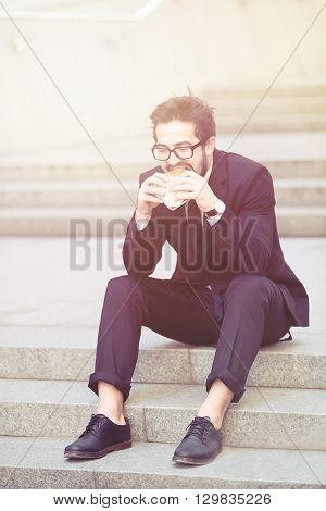 Toned image of handsome businessman in glasses eating junk food while sitting on stairs in city centre. Freelance man in black business suit. Side view.