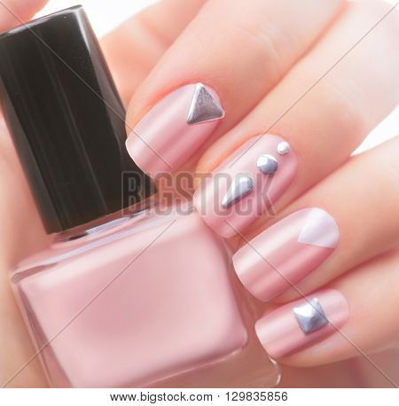 Nail art manicure. Fashion modern design Beige color Manicure with metal accessories. Bottle of Nail Polish. Beauty salon. Hand. Trendy Stylish Colorful Nails, Nailpolish