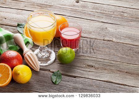 Fresh ripe citruses and juice. Lemons, limes and oranges on wooden background. View with copy space