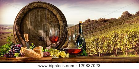 Barrel with glas of red wine and cheese on vineyard
