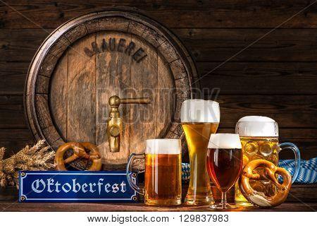 Oktoberfest beer barrel with beer mugs and pretzels on wooden background