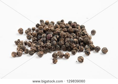Heap of dried black pepper peppercorns isolated on white background