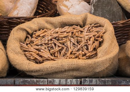 Uncooked Wholemeal Flour Pasta In Jute Bag On Wooden Table