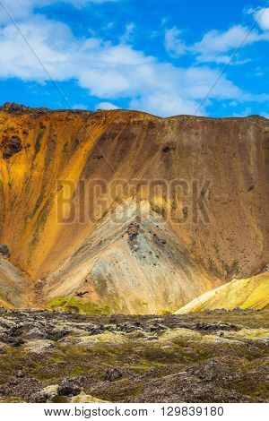 Bright and multi-colored rhyolite mountains - orange, yellow, green and blue. Travel to Iceland in July,  volcanic summer tundra