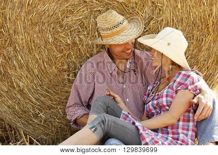a young couple in love on haystacks in cowboy hats