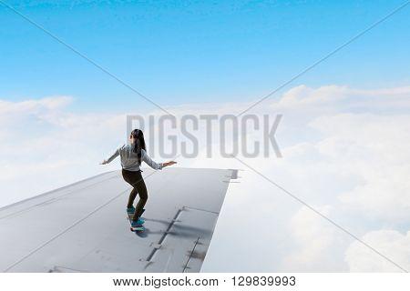 Girl sakting on airplane wing