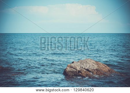 large stone in the sea and skyline filter