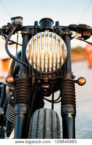 One vintage custom motorcycle cafe racer motorbike with grill headlight on empty rooftop parking lot during sunset. Hipster lifestyle student dream. Lamp is on and directed to camera.