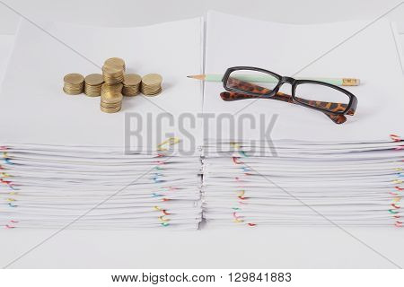 Spectacles and pencil with pile of gold coins place on pile of overload paper and reports with colorful paper clip on white table.