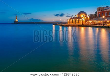 Picturesque view of Venetian quay of Chania with Lighthouse and Kucuk Hasan Pasha Mosque during mornng blue hour before sunrise, Crete, Greece