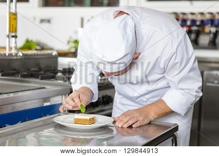 Close-up of a professional male chef who decorates dessert cake with lemon leaf. Large industry kitchen.