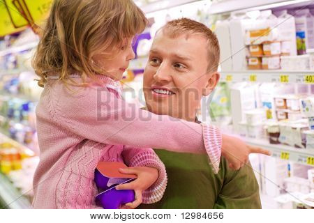 Smiling young man with little girl buy yogurt in supermarket