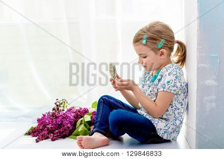 4 years old girl sitting on a windowsill and looking in a small mirror. By lies bouquet of lilacs