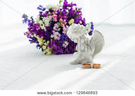 Wedding bouquet, wedding rings, angel on a white background