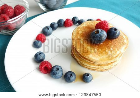 Blueberry pancakes breakfast background with a stack of pancakes fresh berries and maple syrup.