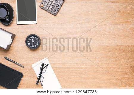 Light wooden tabletop with office tools and black clock on its left side. Topview Mock up