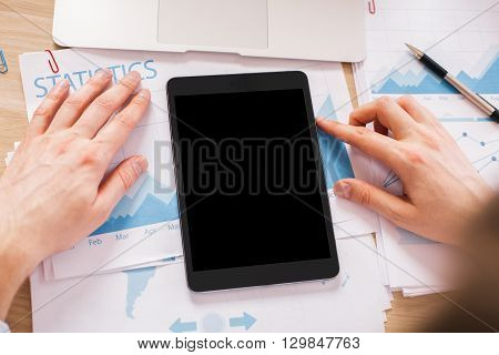 Hands with blank black tablet on wooden desktop with business report on paper sheets. Topview Mock up