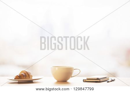 Tabletop with round coffee mug croissant and smartphone with notepad on bright background