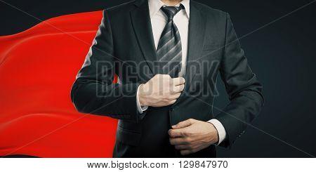 Businessman with red superhero cape on dark background
