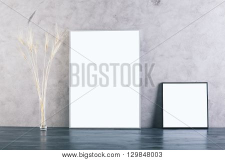 Two blank picture frames and wheat spikes on concrete background. Mock up