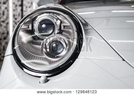 Car detailing series : Closeup of gray car headlights