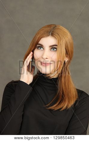 young red beauty communicates by phone. a vertical portrait on a gray background