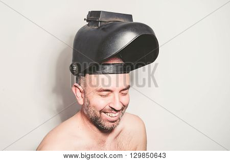 Shirtless man with welding mask over white wall he is laughing