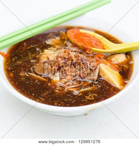 A bowl of Loh mee with chopsicks and a spoonful of chili paste
