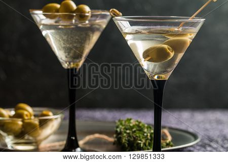 Two glasses of Dry Martini, classic cocktail with olives, vodka and gin served cold