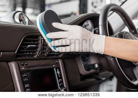 Car detailing series : Closeup of hand cleaning car interior