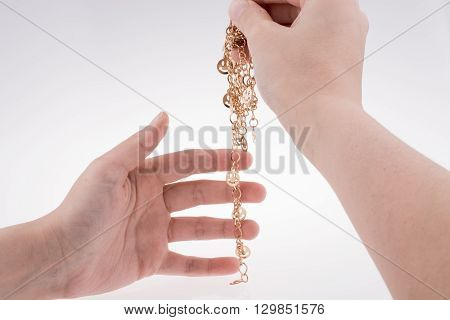 Golden color smileys arrayed on a chain in hand