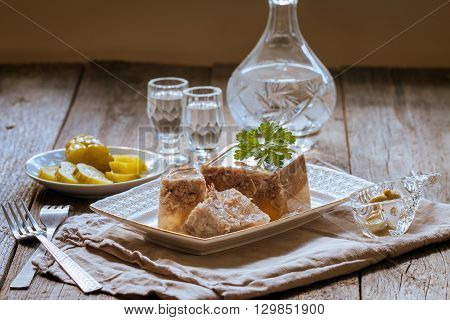 Jellied meat on the white plate with salted cucumbers, bread and vodka  on linen tablecloth background
