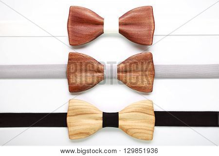 Three wooden bow ties with white, grey and black ribbons. Flat lay, isolated. Team work, career, hipster, wedding concept. White stripe, black stripe.