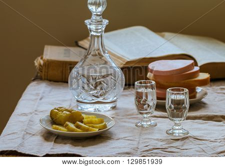 Pickled cucumbers on the plate with decanter of russian vodka and vodka two shots retro stile