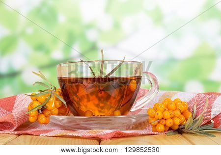 Ripe sea buckthorn berries and a cup of tea on the abstract green background.