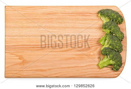 Wooden cutting board with pieces of fresh broccoli isolated on white background.