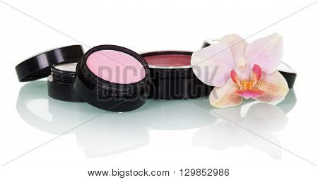 Professional makeup: eye shadow, blush and orchid flower isolated on white background.