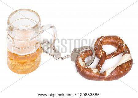 pretzel chained with handcuffs to beer mug over white