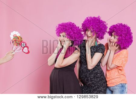 Portrait of a young women wearing a carnival wigs and surprised by some candy offer.