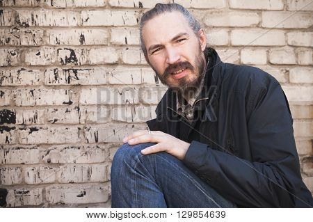 Bearded Asian Man In Black Over Gray Urban Wall