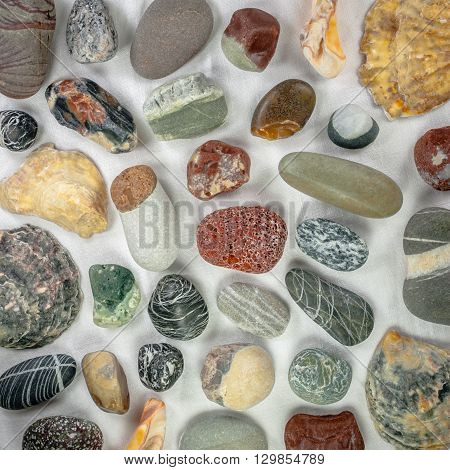 sea stones and seashells on white canvas background, perfect background for your concept or project