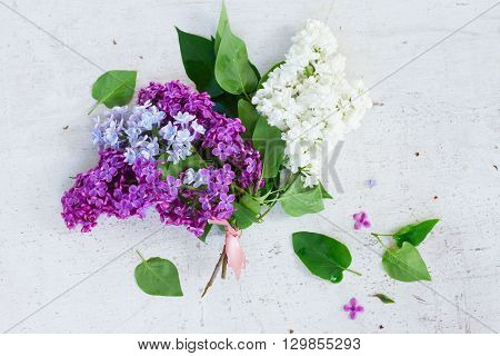 Posy of fresh lilac flowers on white wooden table