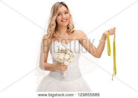 Cheerful young bride in a white wedding dress holding a measuring tape isolated on white background